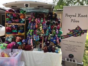The back of a van opened up and full of an overflowing yarn display, along with a sign for Frayed Knot Fibre
